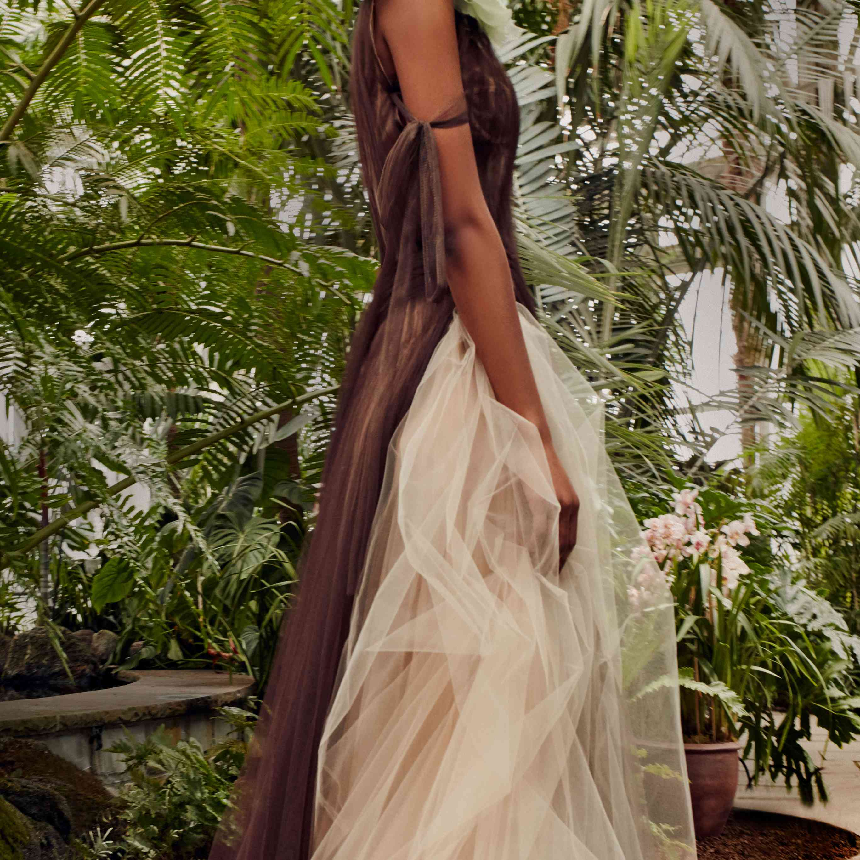 Model in a brown dress with a tulle nude exposed underskirt and a light green flower accent at the shoulder