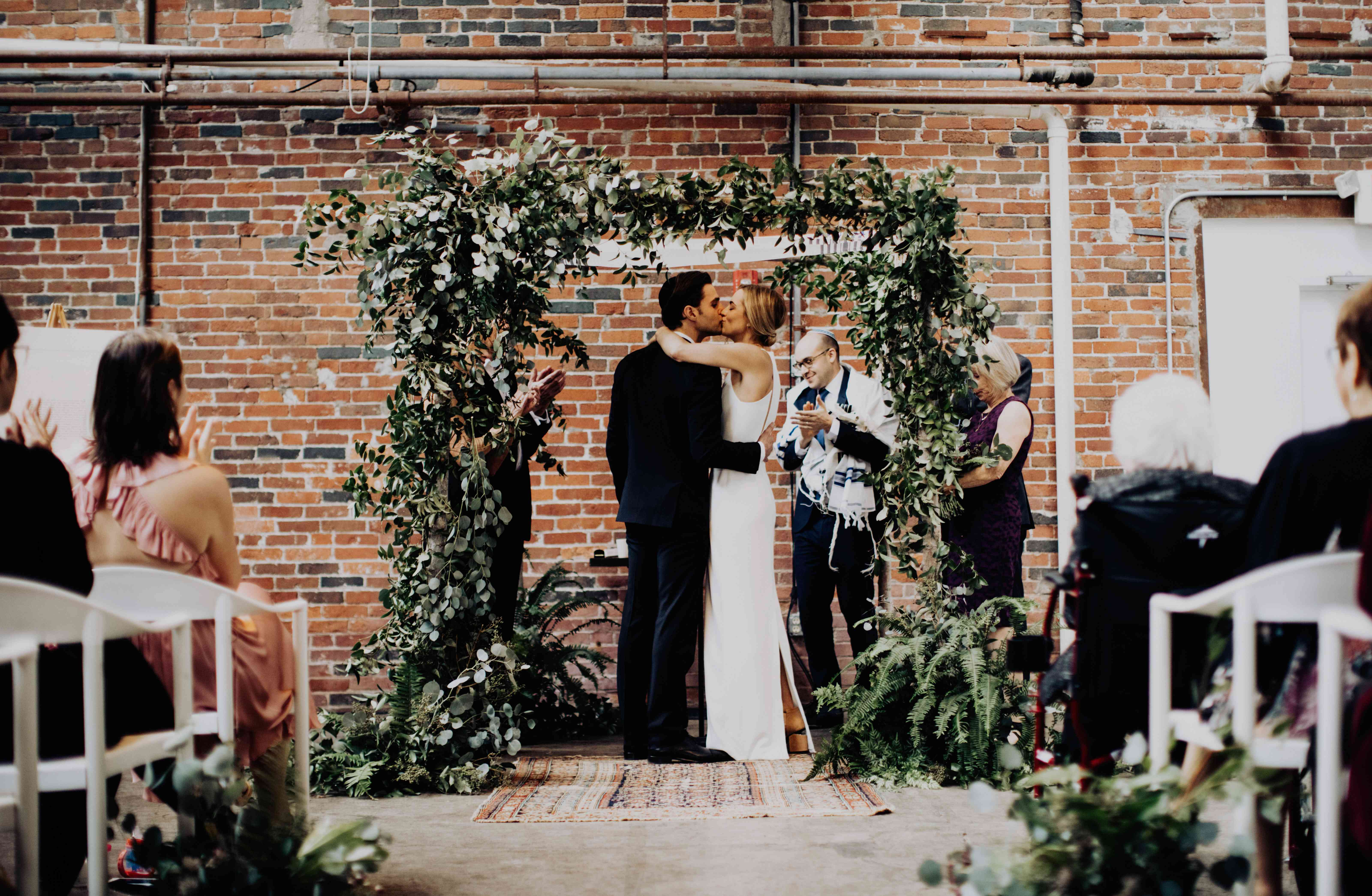 Bride and groom sharing kiss under floral altar