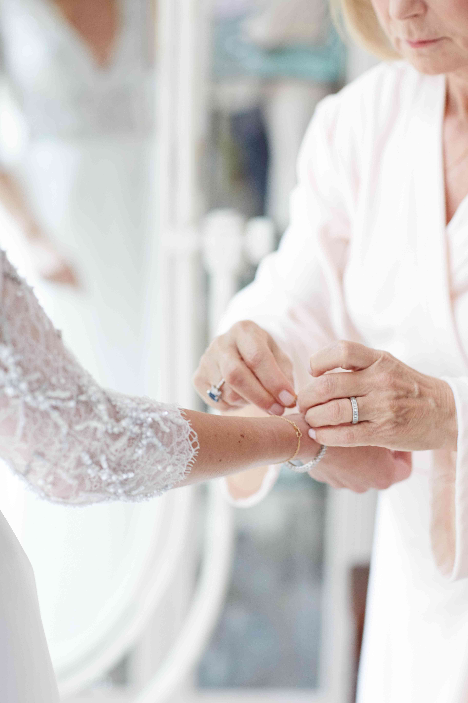 Mom putting jewelry on bride