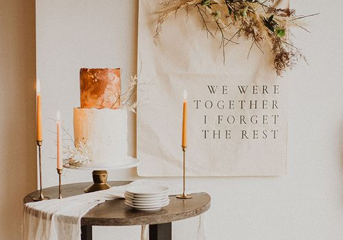 Round table with wedding cake and stick candles with plates in front of wedding banner sign on wall