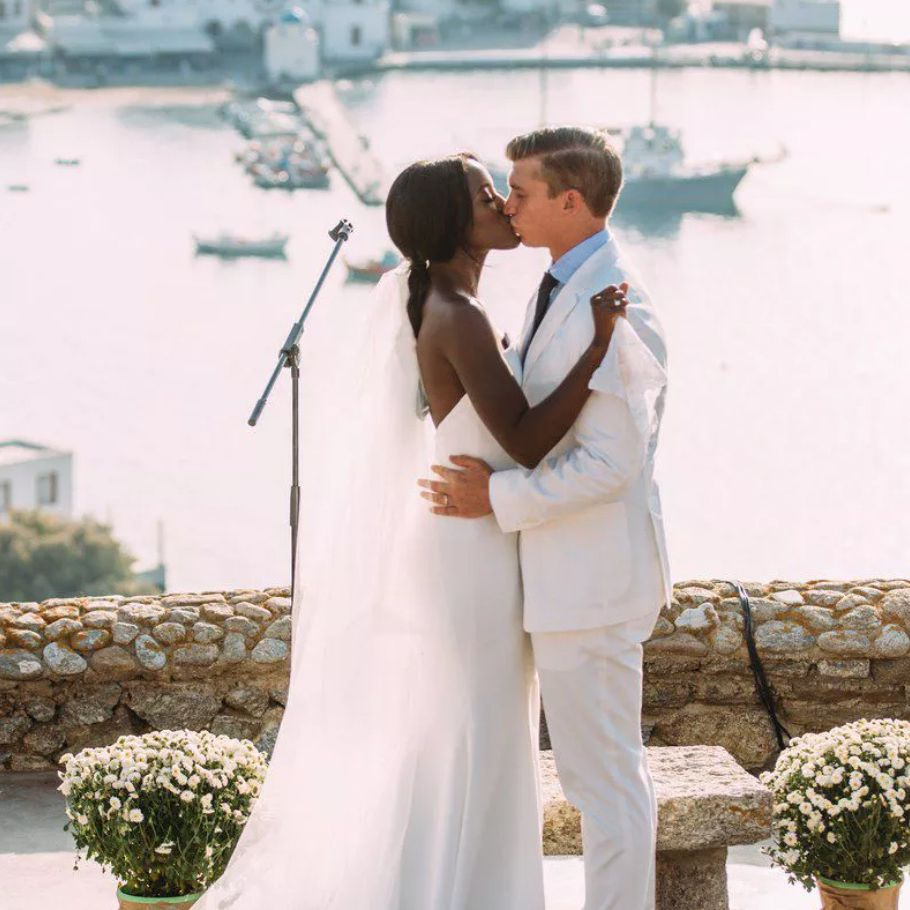 Newlyweds kissing in front of ocean
