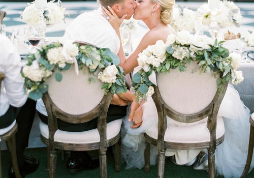 Bride and groom kissing while sitting at the head table at the wedding reception