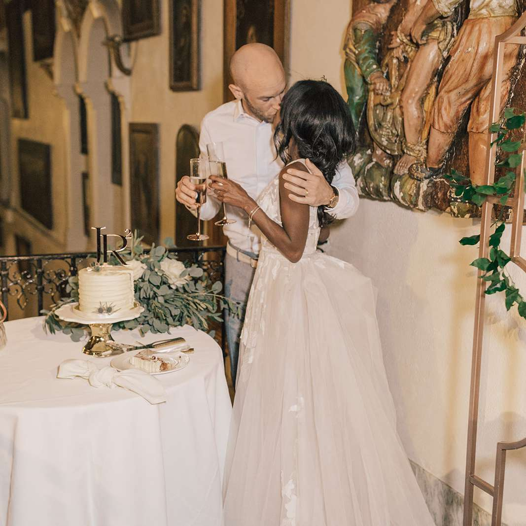 couple kissing during cake cutting