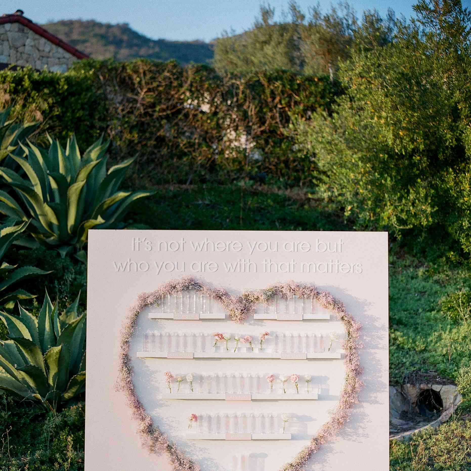 Escort card display with a flowers in the shape of a heart that says