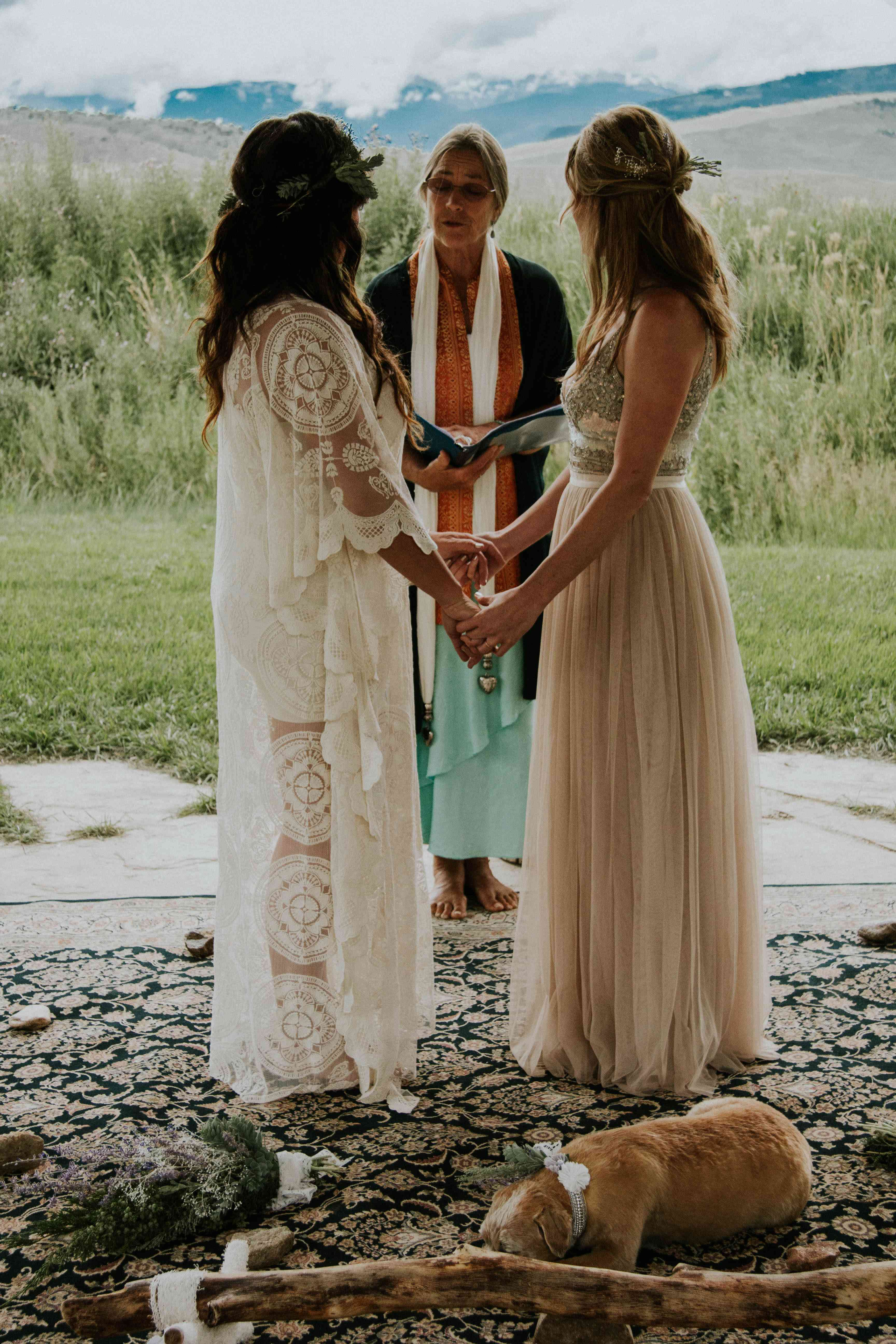 Brides holding hands at ceremony