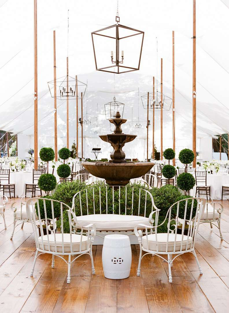 Interior of a wedding venue with white chairs and a bench