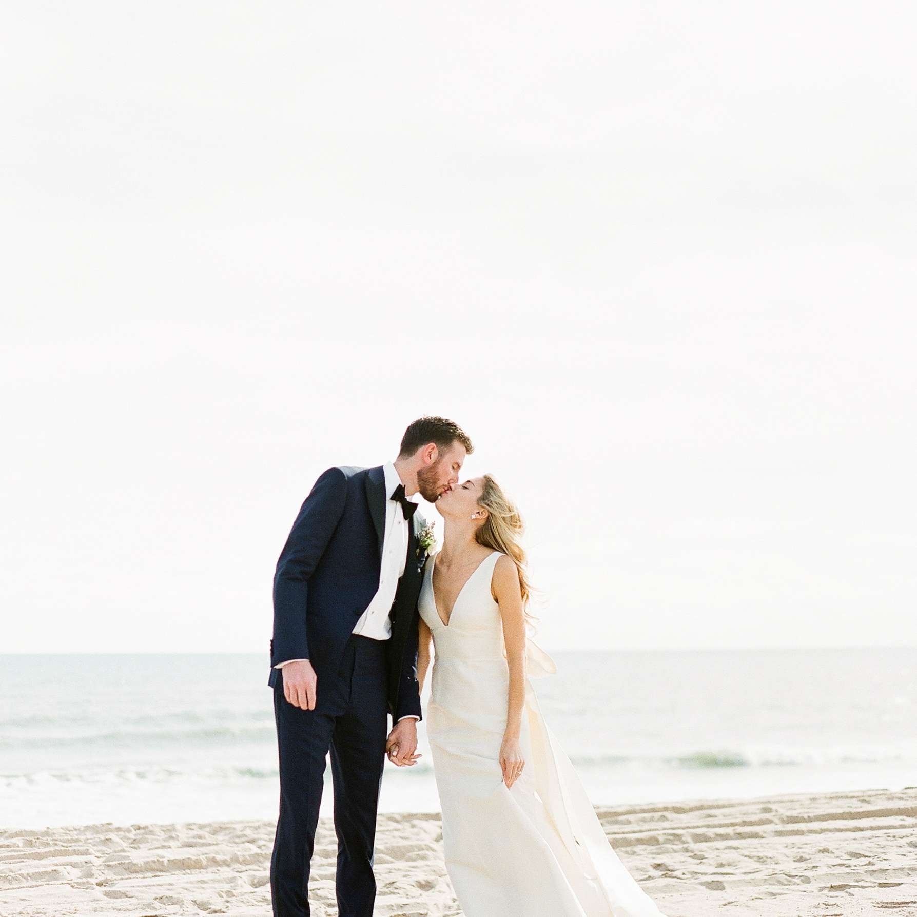 <p>bride and groom kissing on beach</p><br><br>