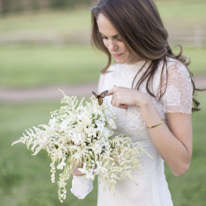 Bride holding an all white bouquet with a butterfly landed on it