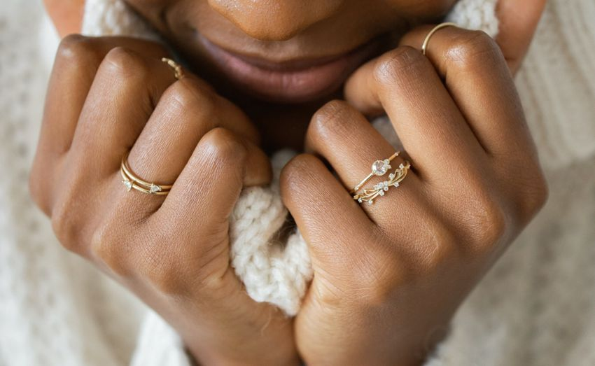 Bride holding sweater with rings on fingers