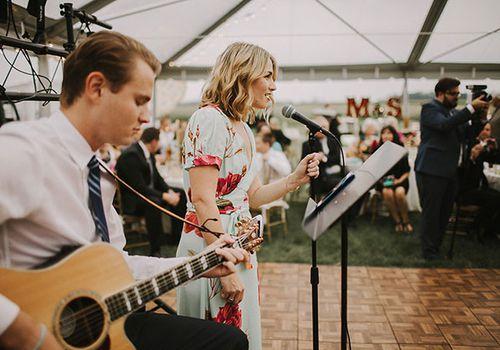 Man playing guitar and woman singing at a wedding