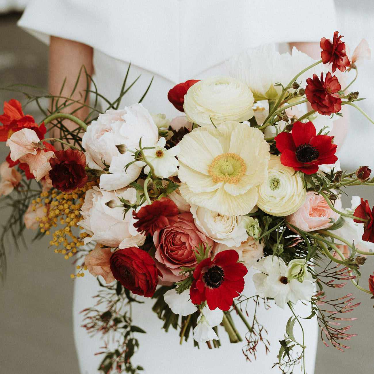 Bride holding a bouquet of red and white poppies