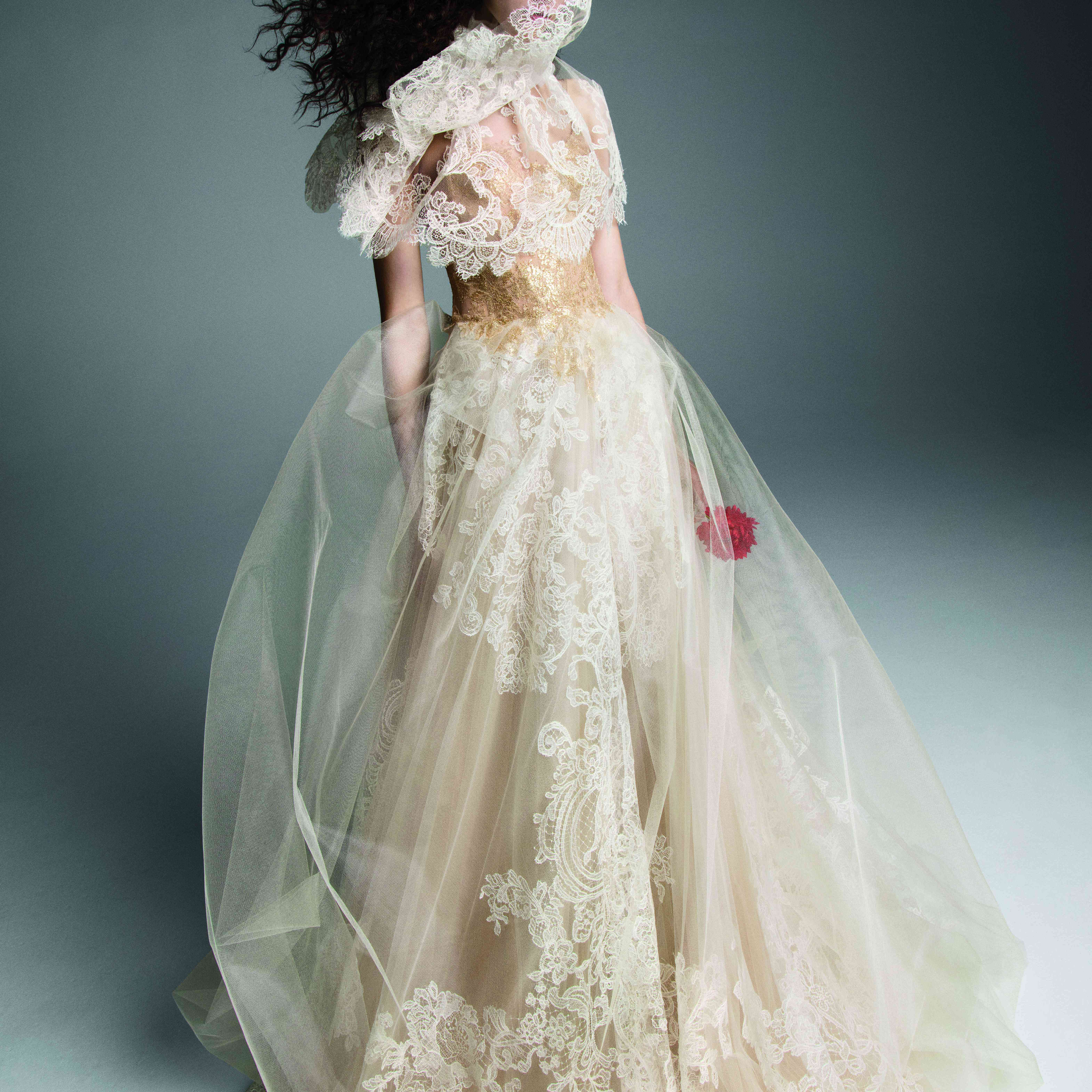 Model in nude and ivory tulle A-line gown with gold lace accents on the bodice and white lace along the skirt