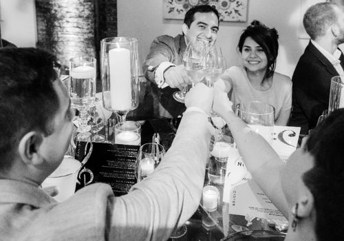 Four people toasting at a wedding rehearsal dinner
