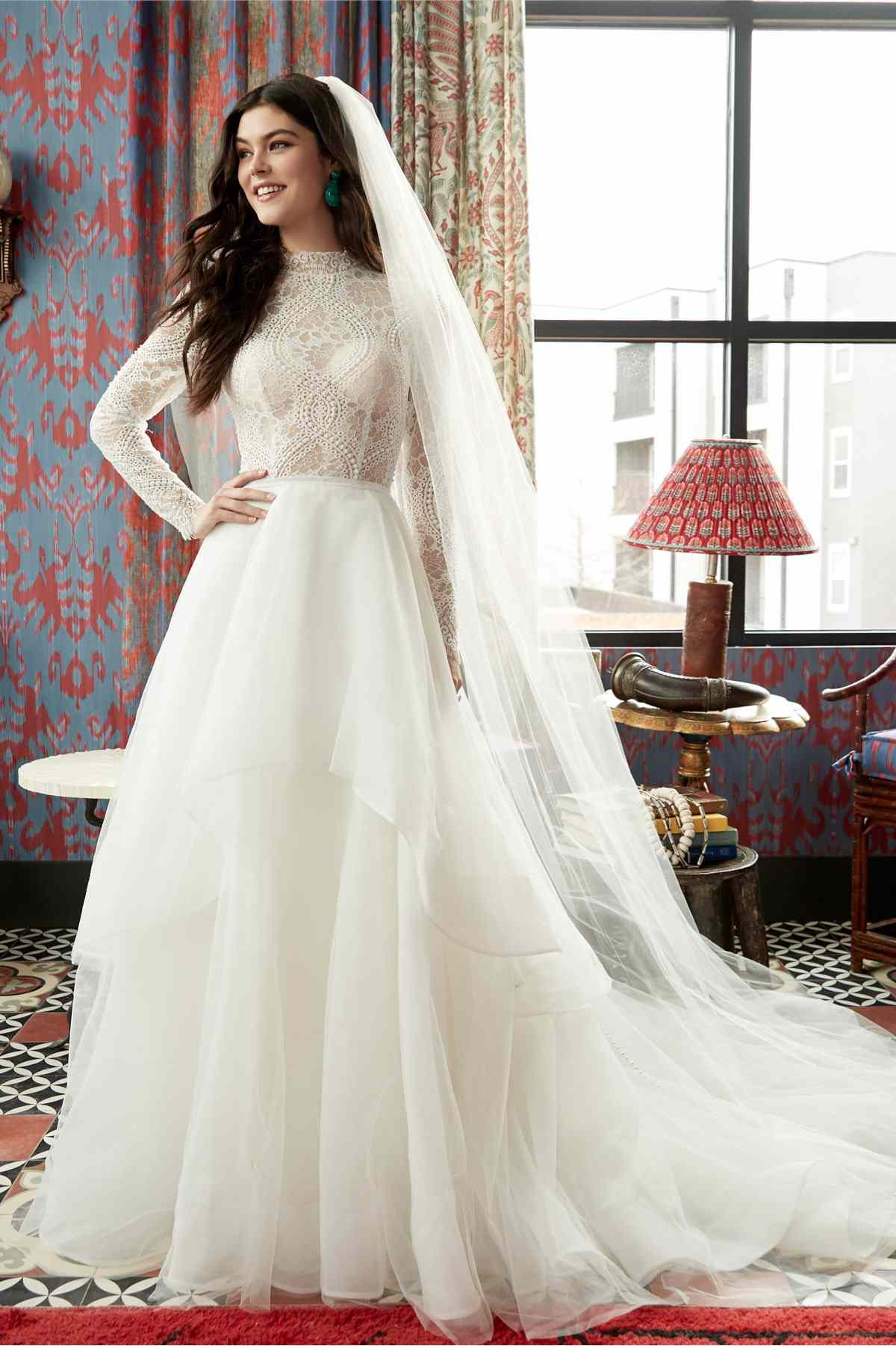 Model in ballgown with long-sleeved mock-neck lace bodice and tiered skirt