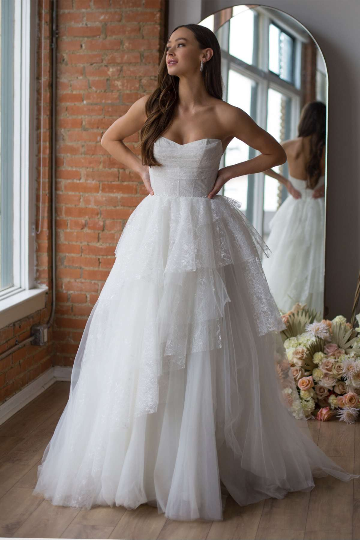 Model in strapless sweetheart lace ballgown with a tiered skirt