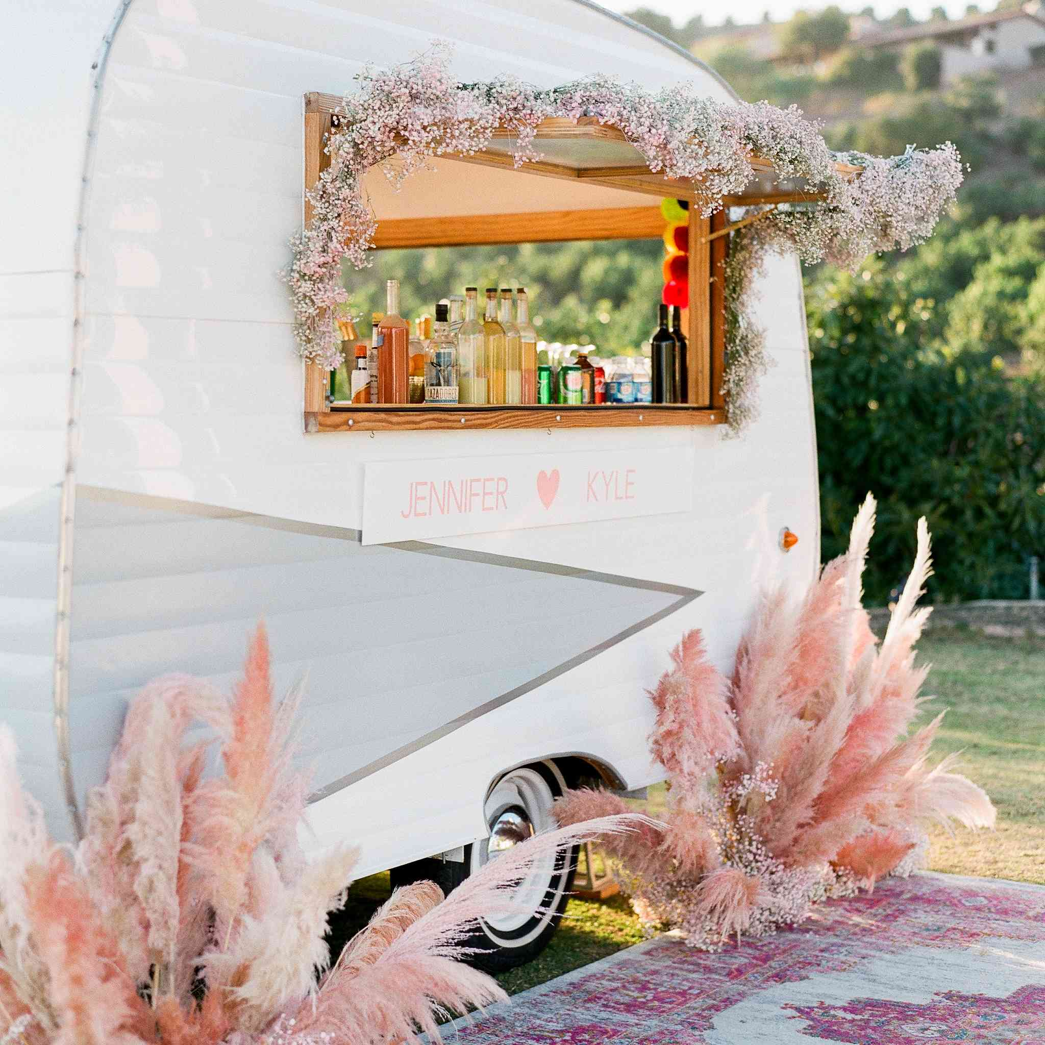 A mobile bar cart decorated with pink baby's breath and pink pampas grass