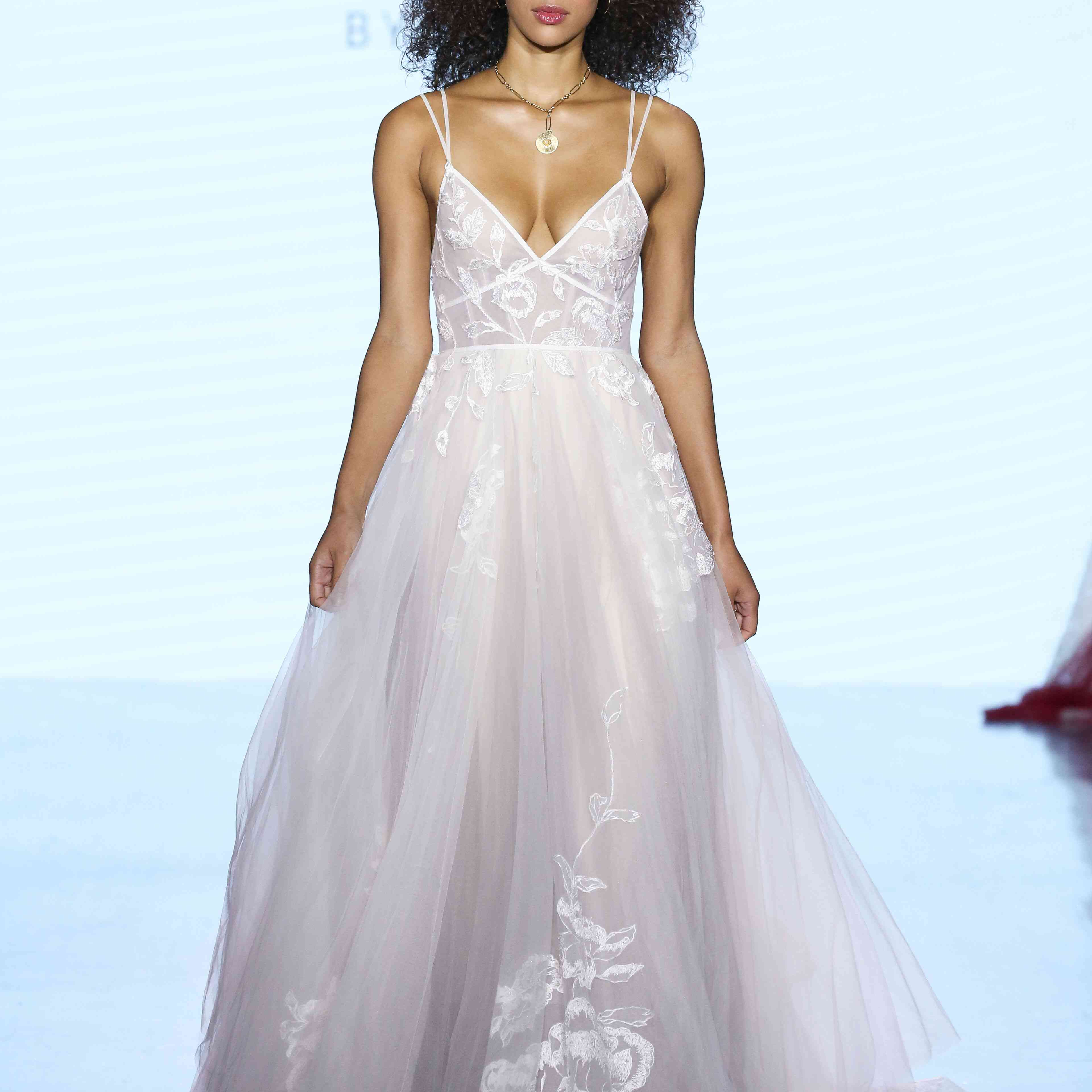 Model in tulle wedding dress with floral lace embroidery, V-neckline, and double spaghetti straps