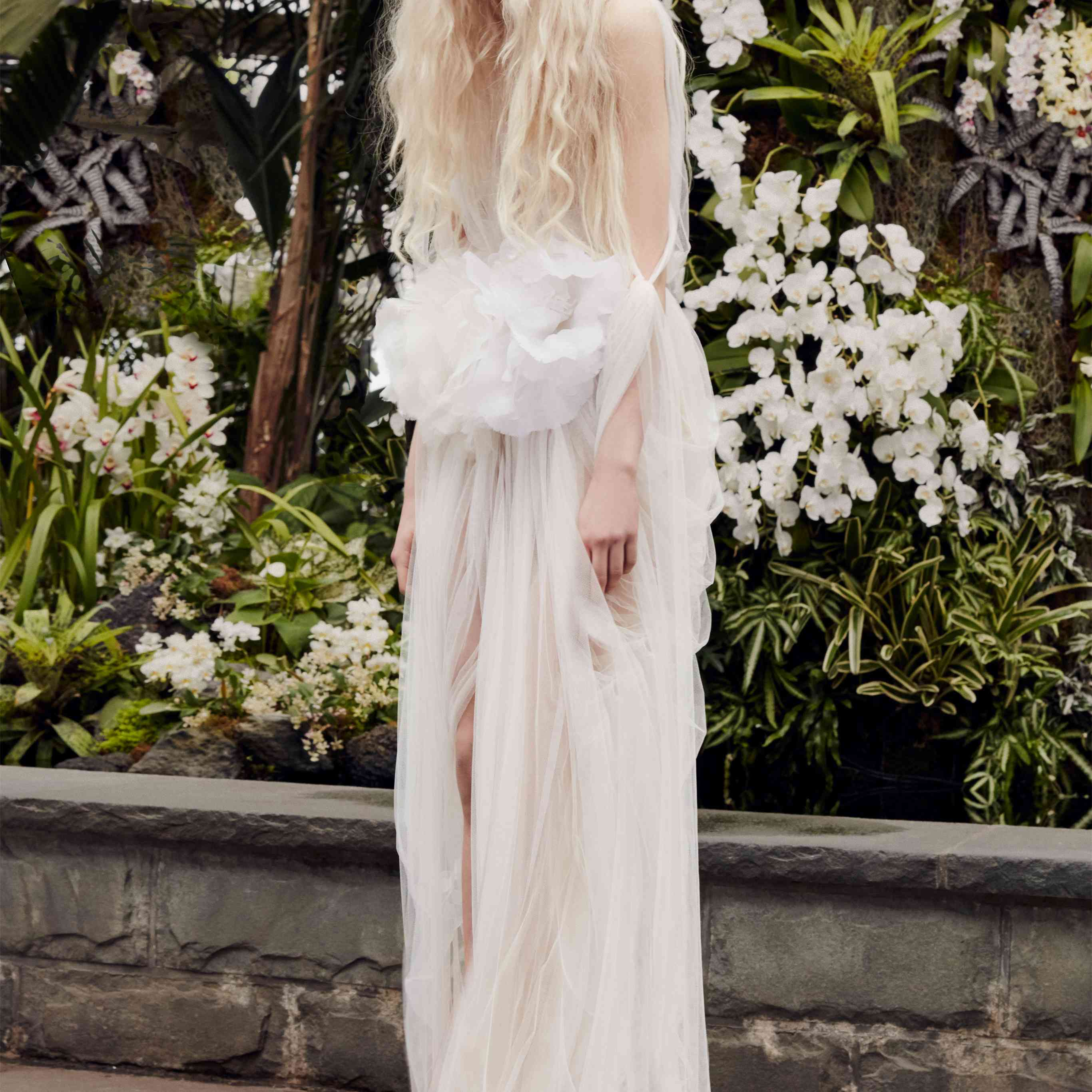 Model in a white wispy tulle gown with flower details at the waist