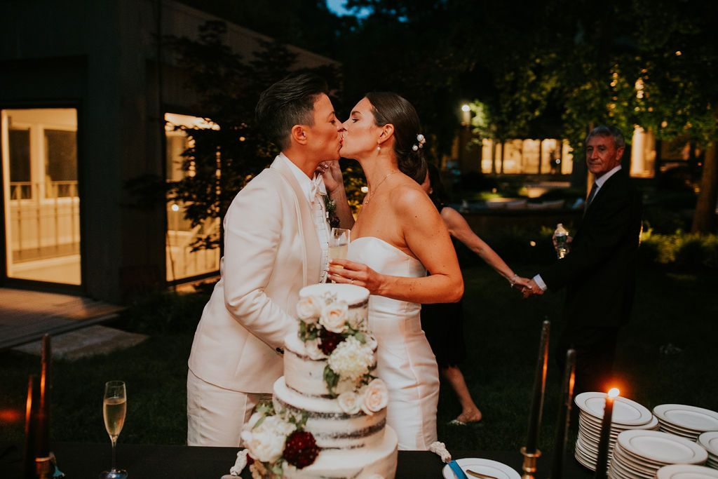 The couple kiss during the cake cutting