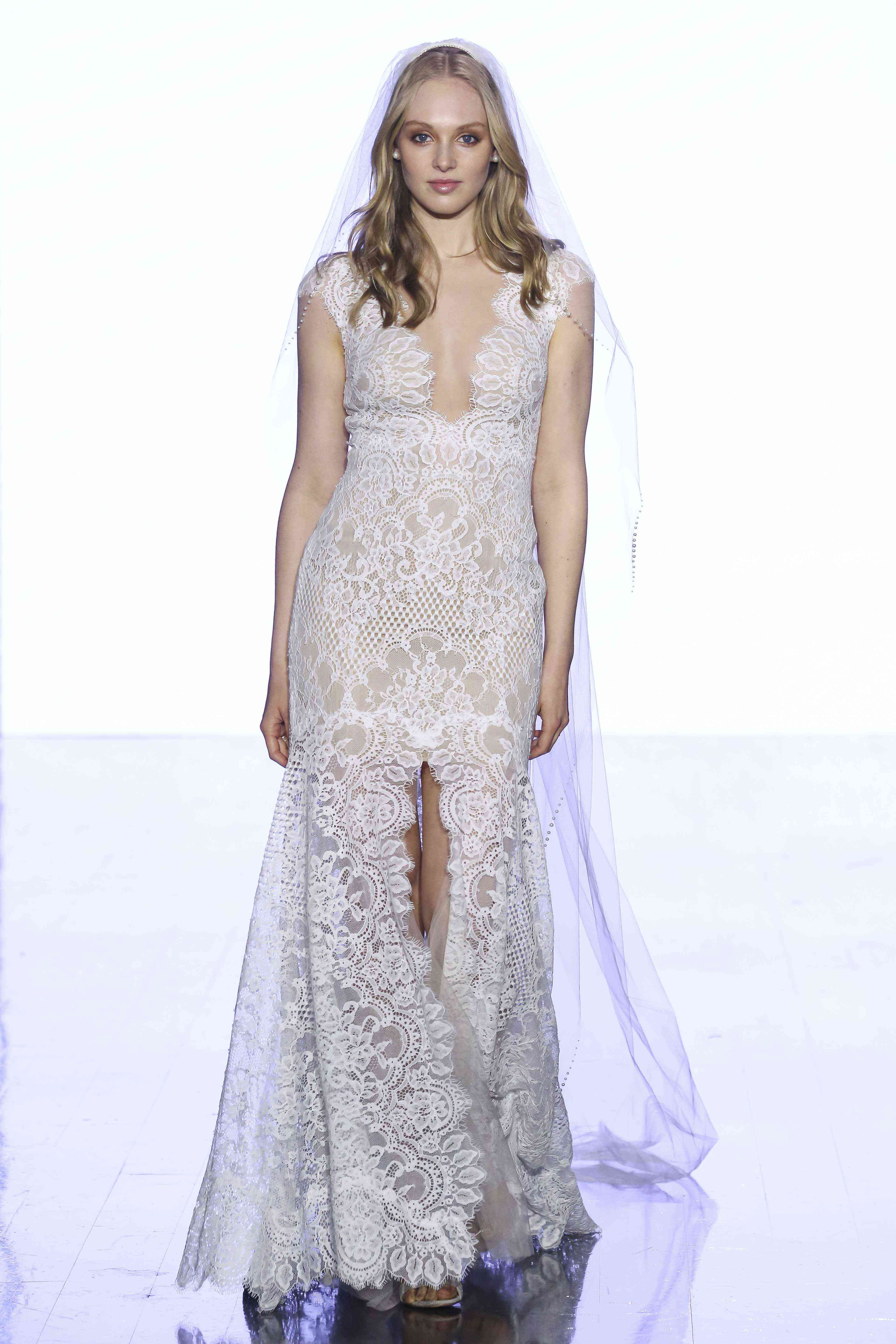 Model in allover lace sheath gown with a plunging neckline, cap sleeves, and front slit
