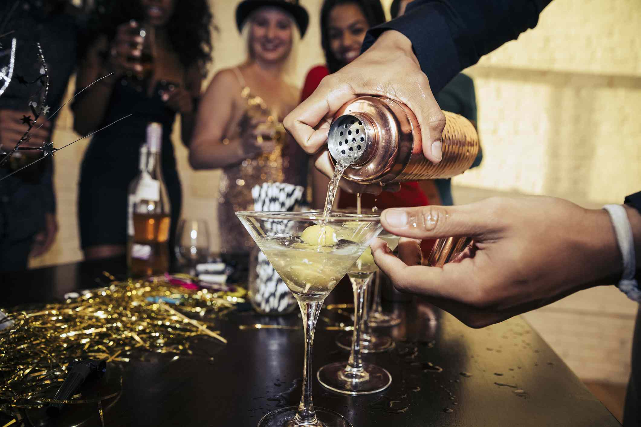 Person pouring cocktail while friends watch in the background at a party