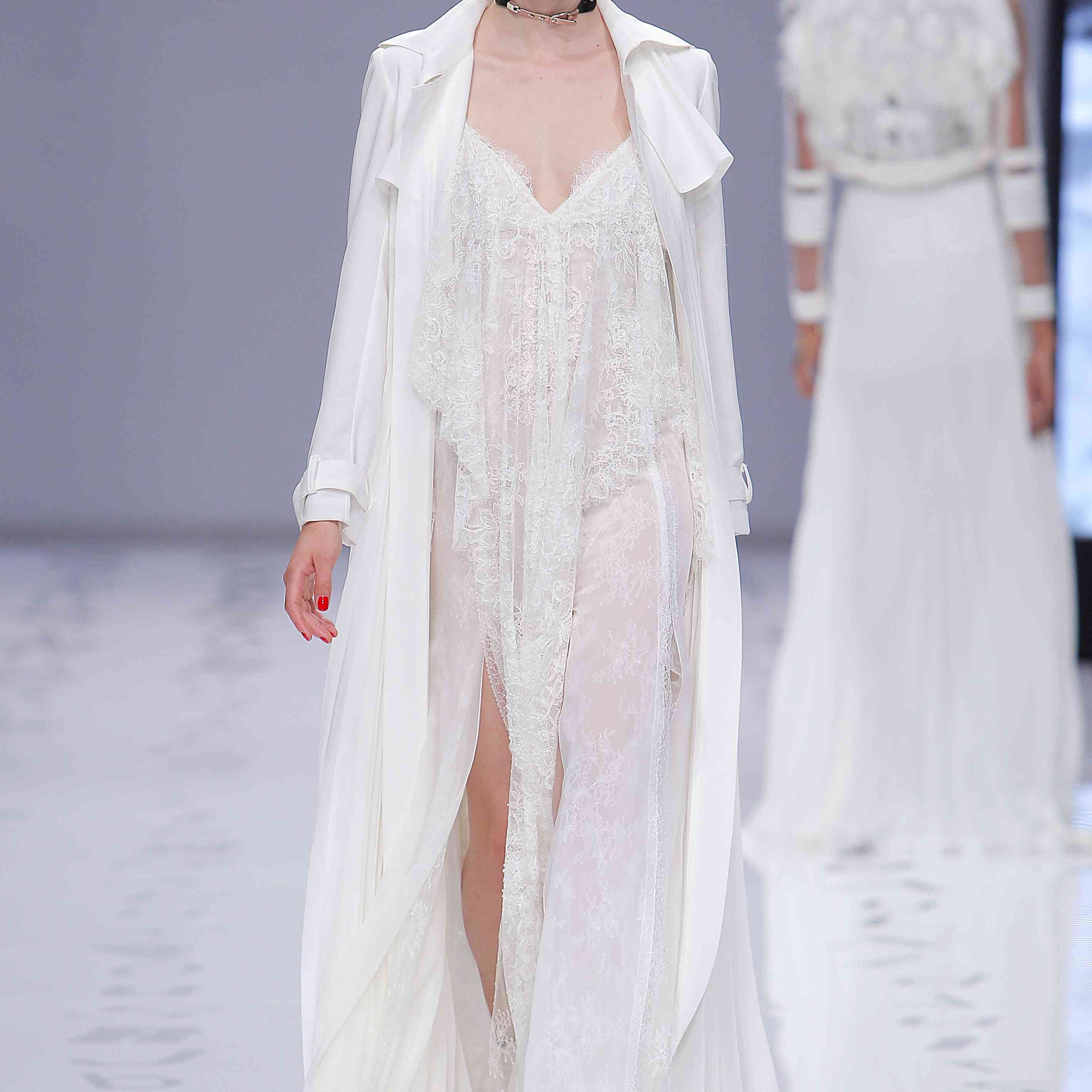Model in a lace V-neck slip dress with a front slit worn with a floor-length blazer