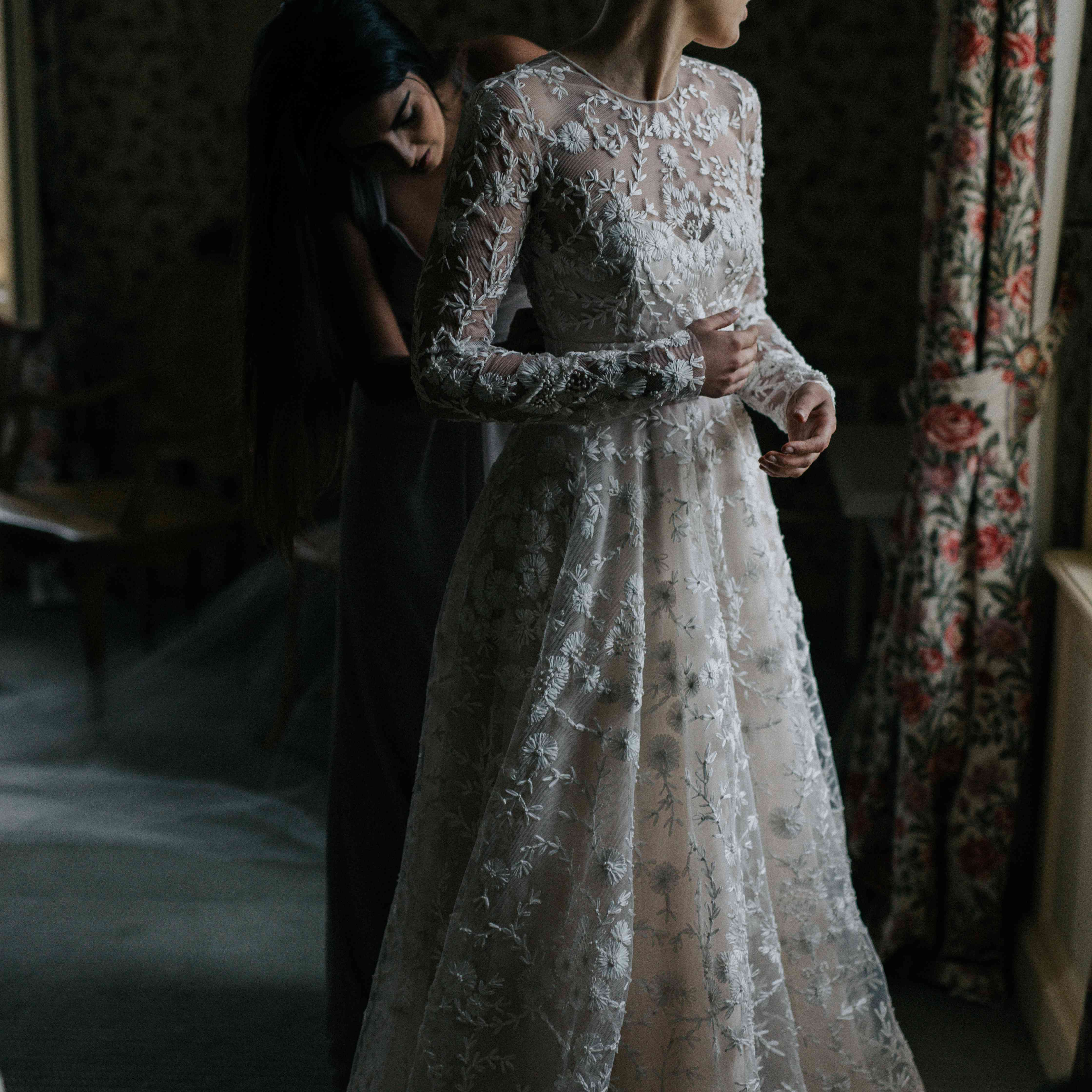 helping the bride getting ready long sleeve wedding dress