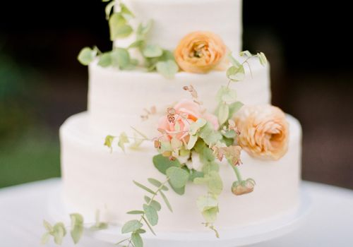 Simple wedding cake with peach flowers and greenery