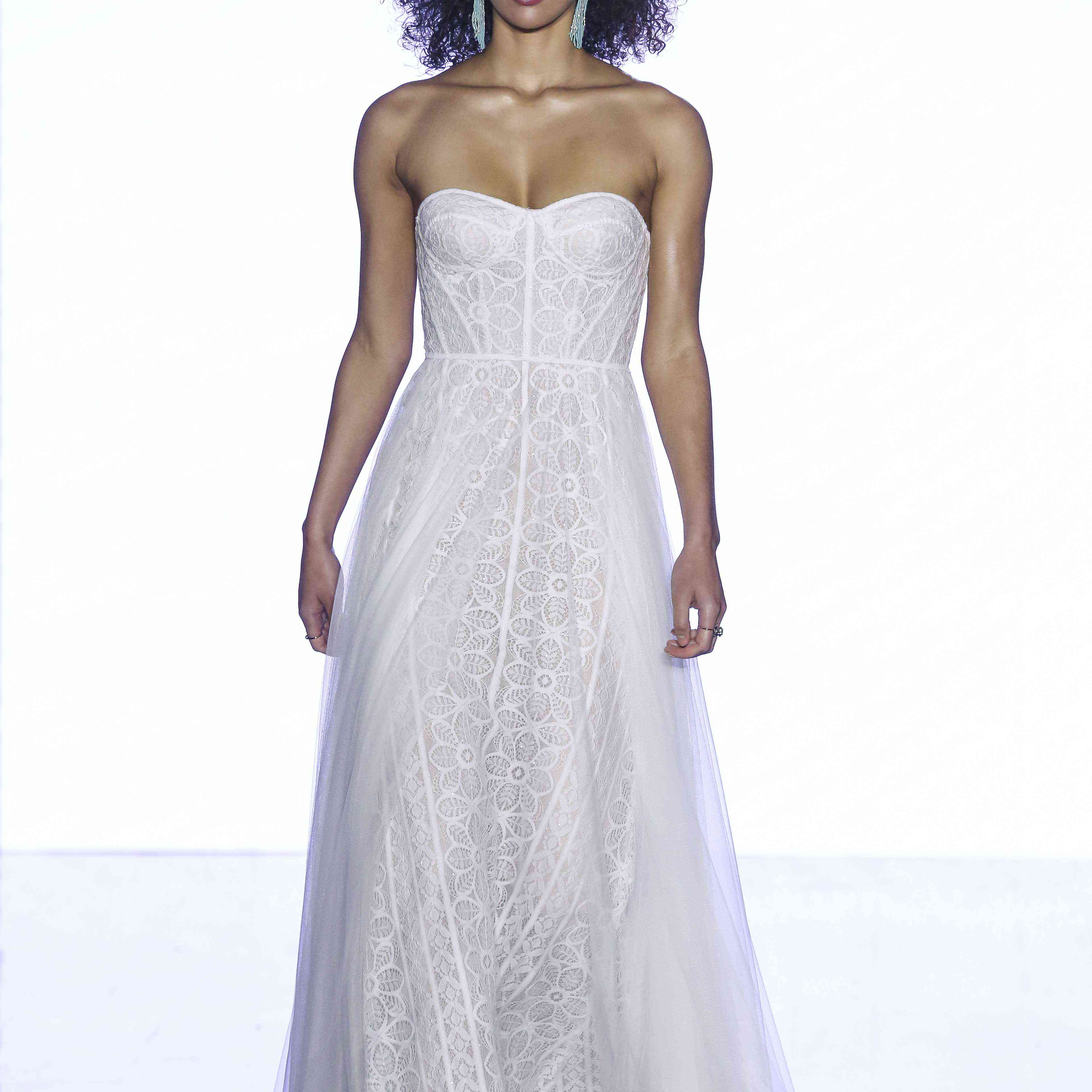 Model in strapless lace A-line gown with structured bodice and netting and tulle skirt overlay