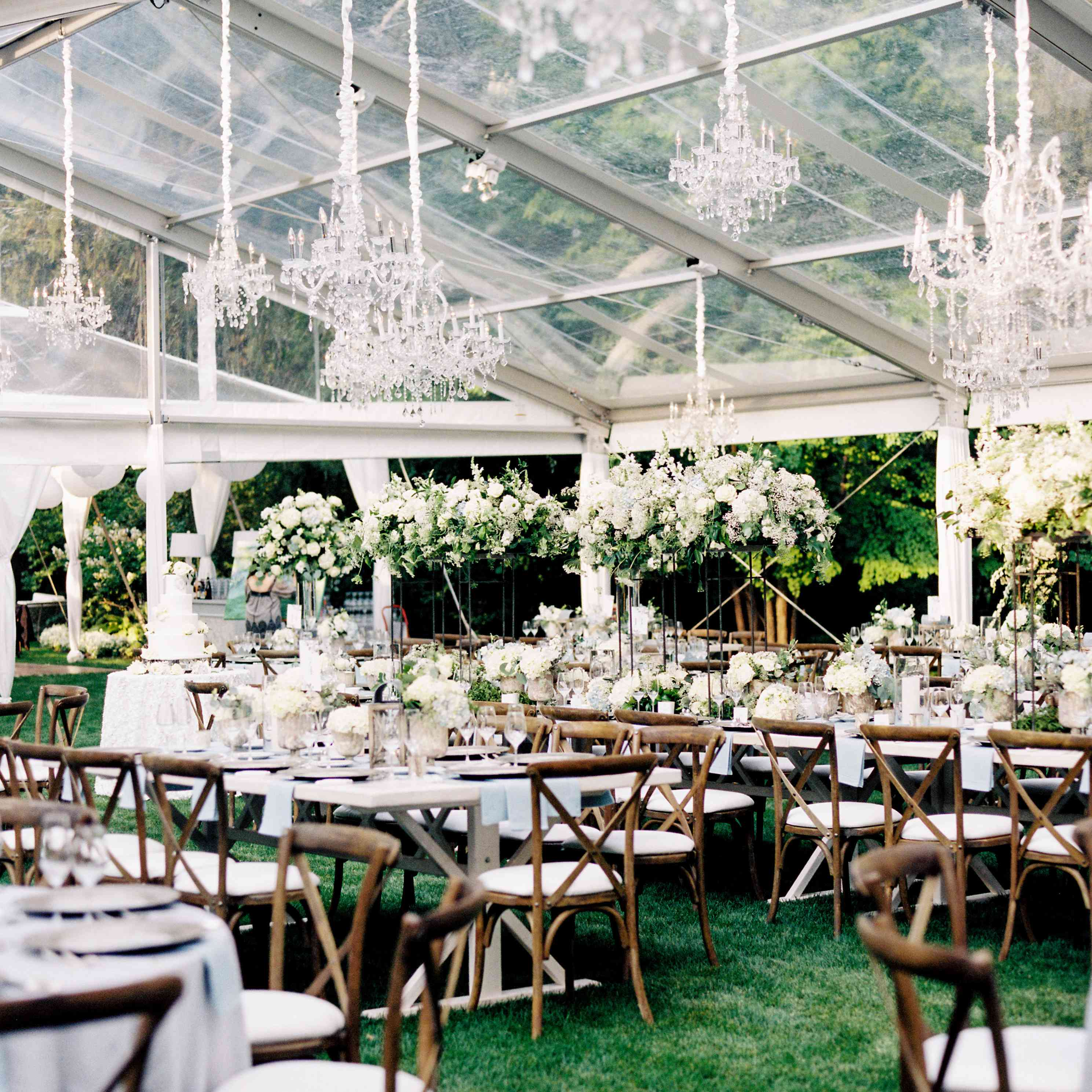 clear tent with chandeliers and wooden chairs