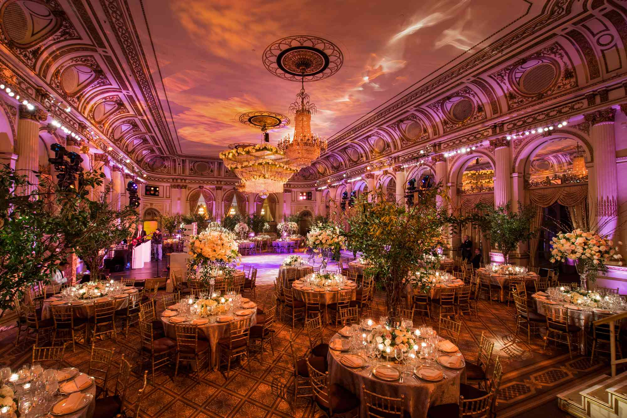 Grand indoor wedding reception featuring uplighting, chandeliers, and tall centerpieces