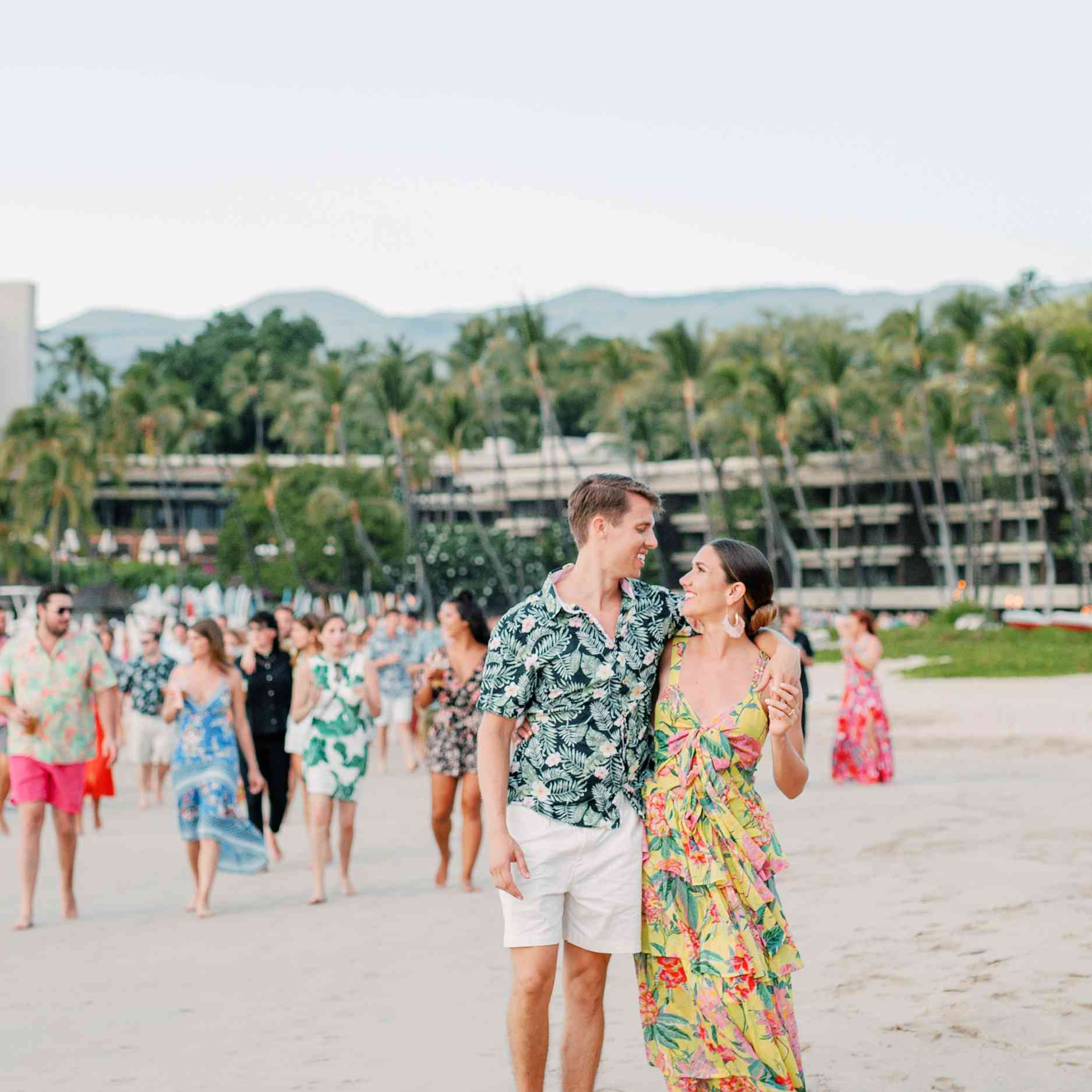 Bride and groom in casual clothing walking on the beach with a group of people walking behind them