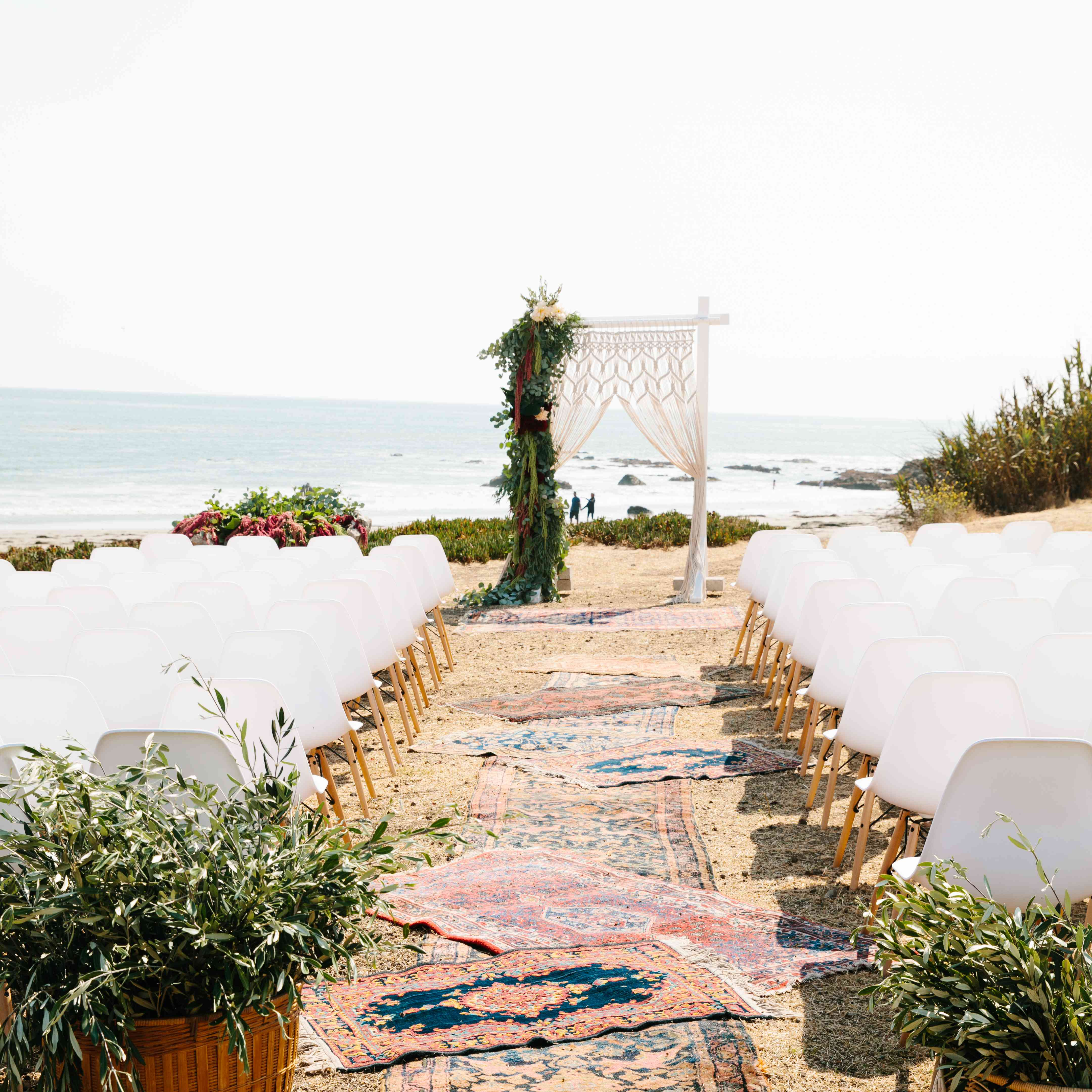Wedding aisle on the beach with multiple rugs lining the aisle