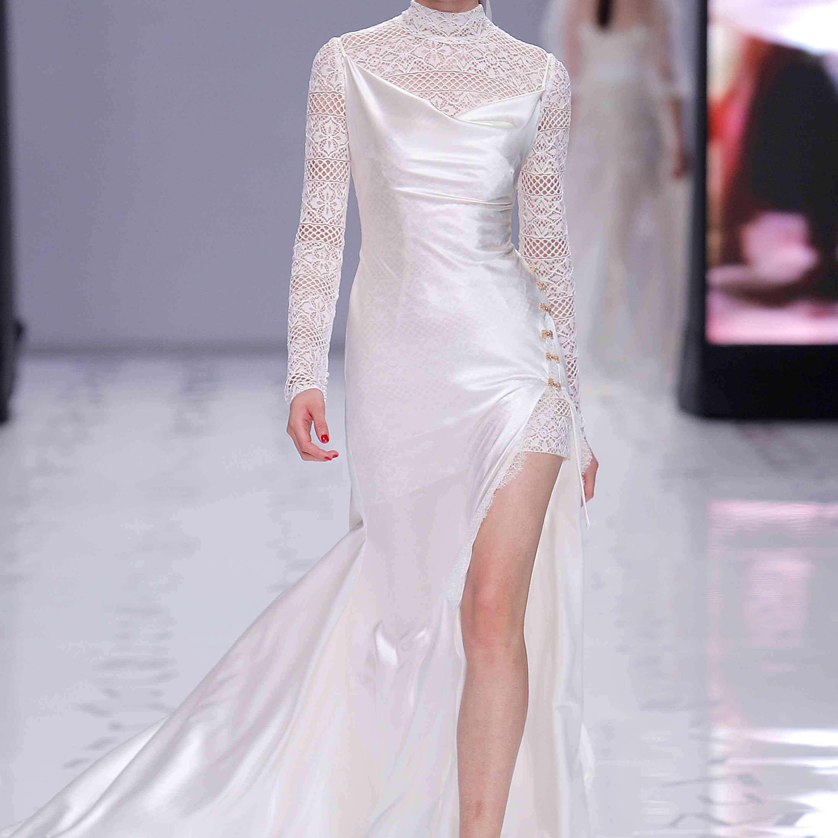 Model in a satin mermaid gown with a high front slit over a mock-neck long-sleeved lace mini dress