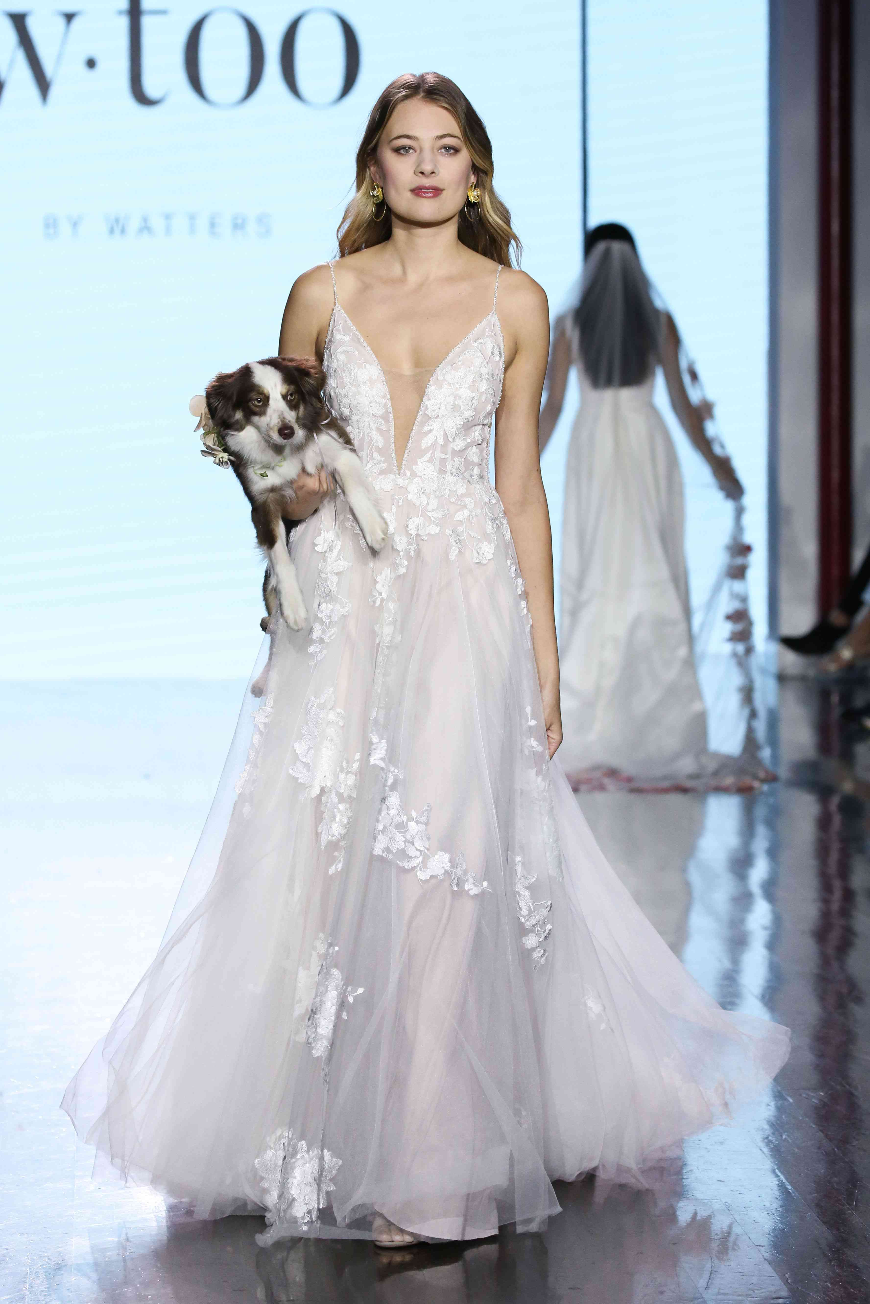 Model in tulle wedding dress with a plunging V neckline, lace appliques and beaded straps