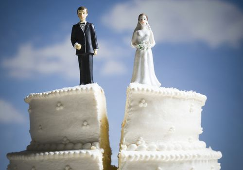 A wedding cake cut in half with a bride and groom on opposite sides.