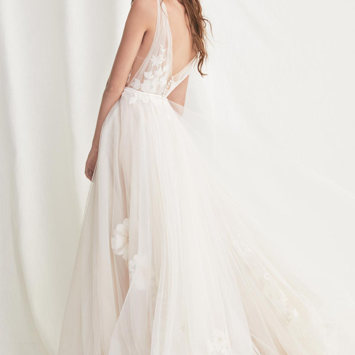 Model in low-back white tulle wedding gown with floral embellishment