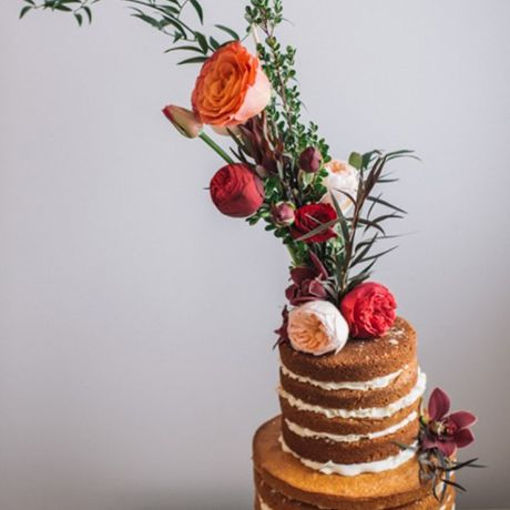 A naked wedding cake topped with a straight-from-the-garden bouquet of greenery