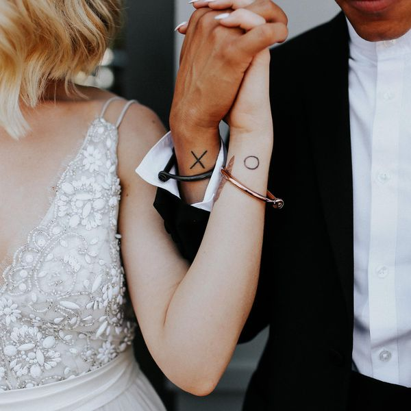 X and O tattoos on forearms of couple getting married