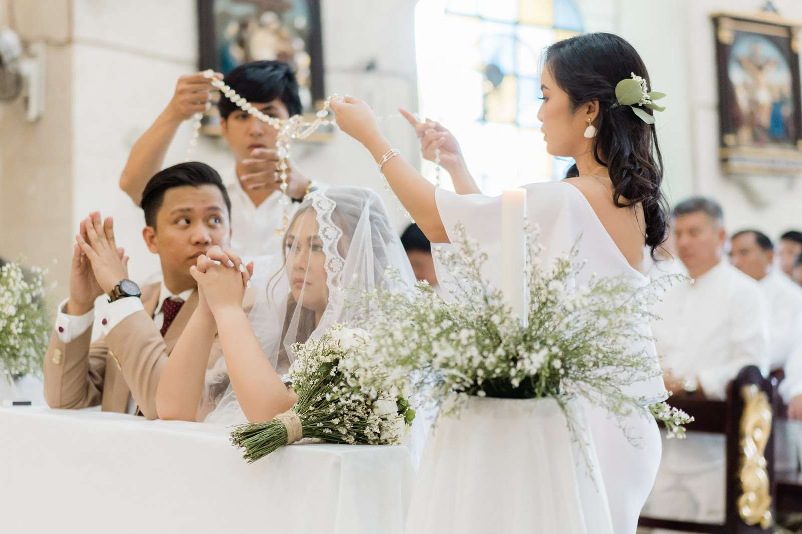people placing cord over bride and groom