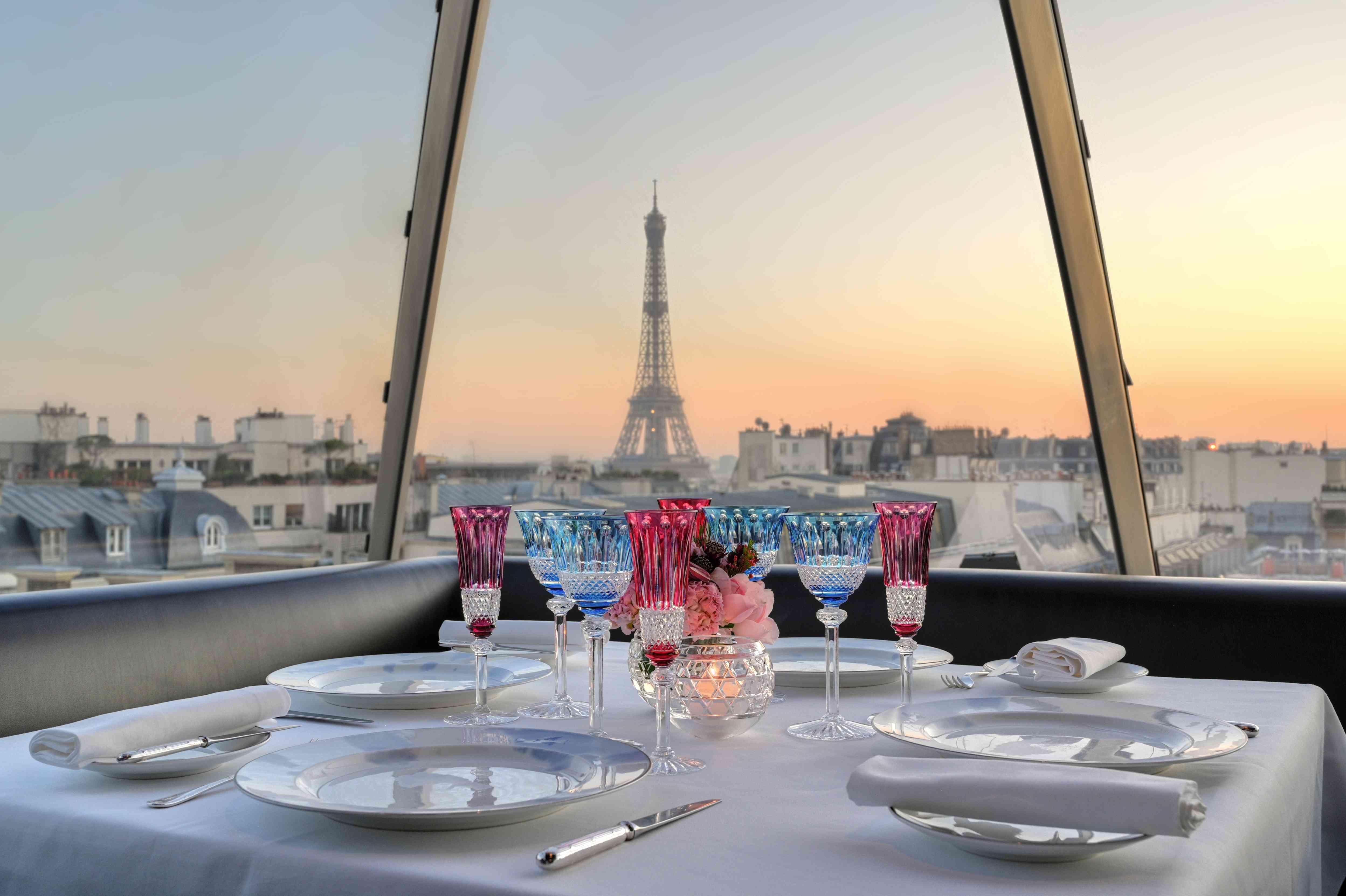 Dinner table with blue and pink glassware in front of window with view of Eiffel Tower at sunset