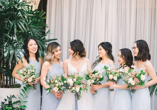 Bridesmaids with pale blue dresses standing with bride