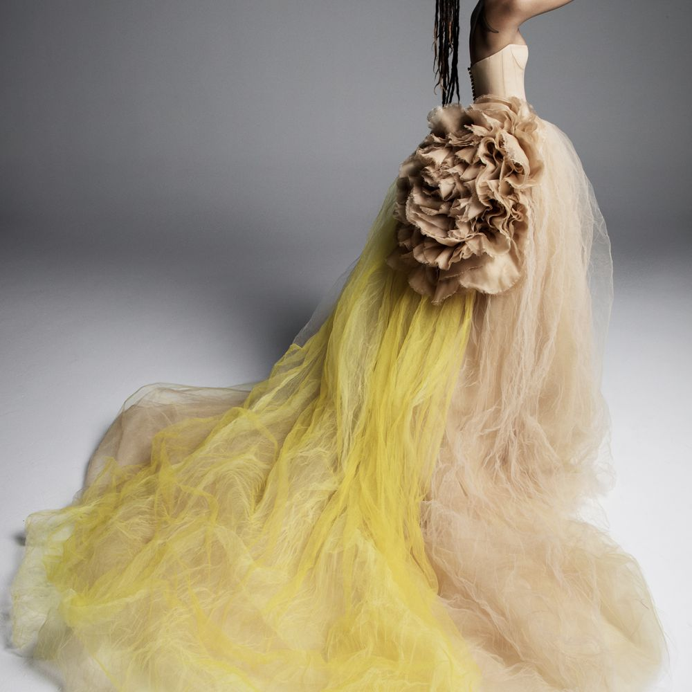 Model in light brown strapless ballgown with a bright yellow train and a ruffled floral accent