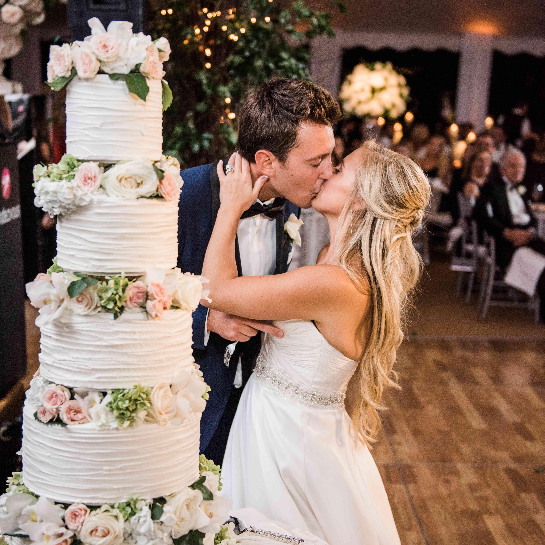 Couple kissing next to wedding cake