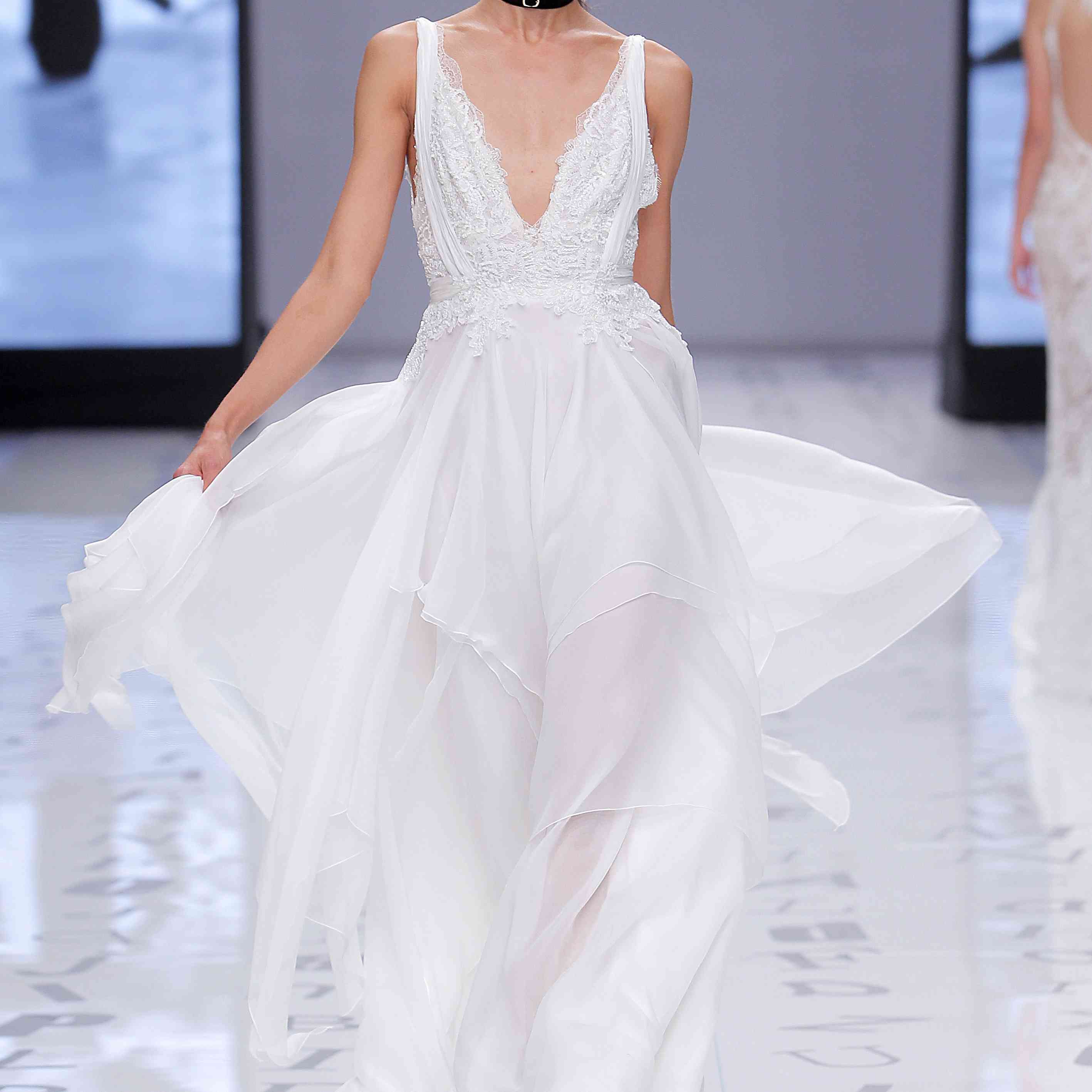 Model in V-neck organza gown with a tiered skirt and floral lace bodice