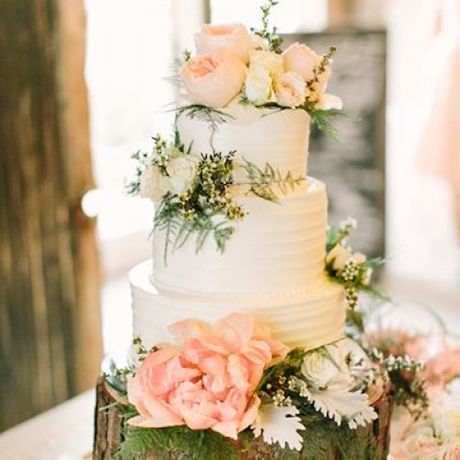 A three-tiered white wedding cake covered in blush blooms by Virginia's Cakes , sitting on a tree stump cake display
