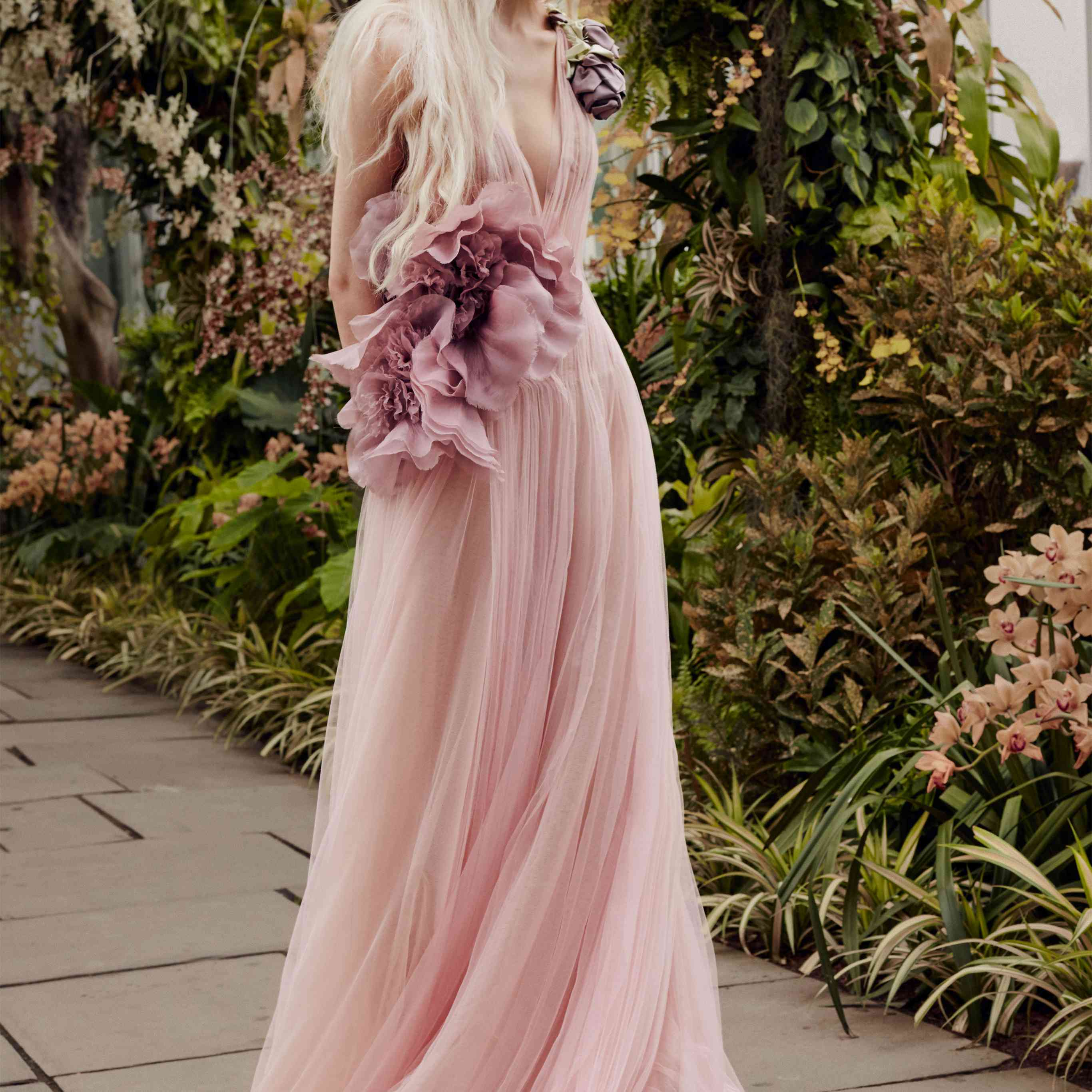 Model in pink V-neck tulle gown with pink flower accents at the waist and a lavender floral accent at the shoulder