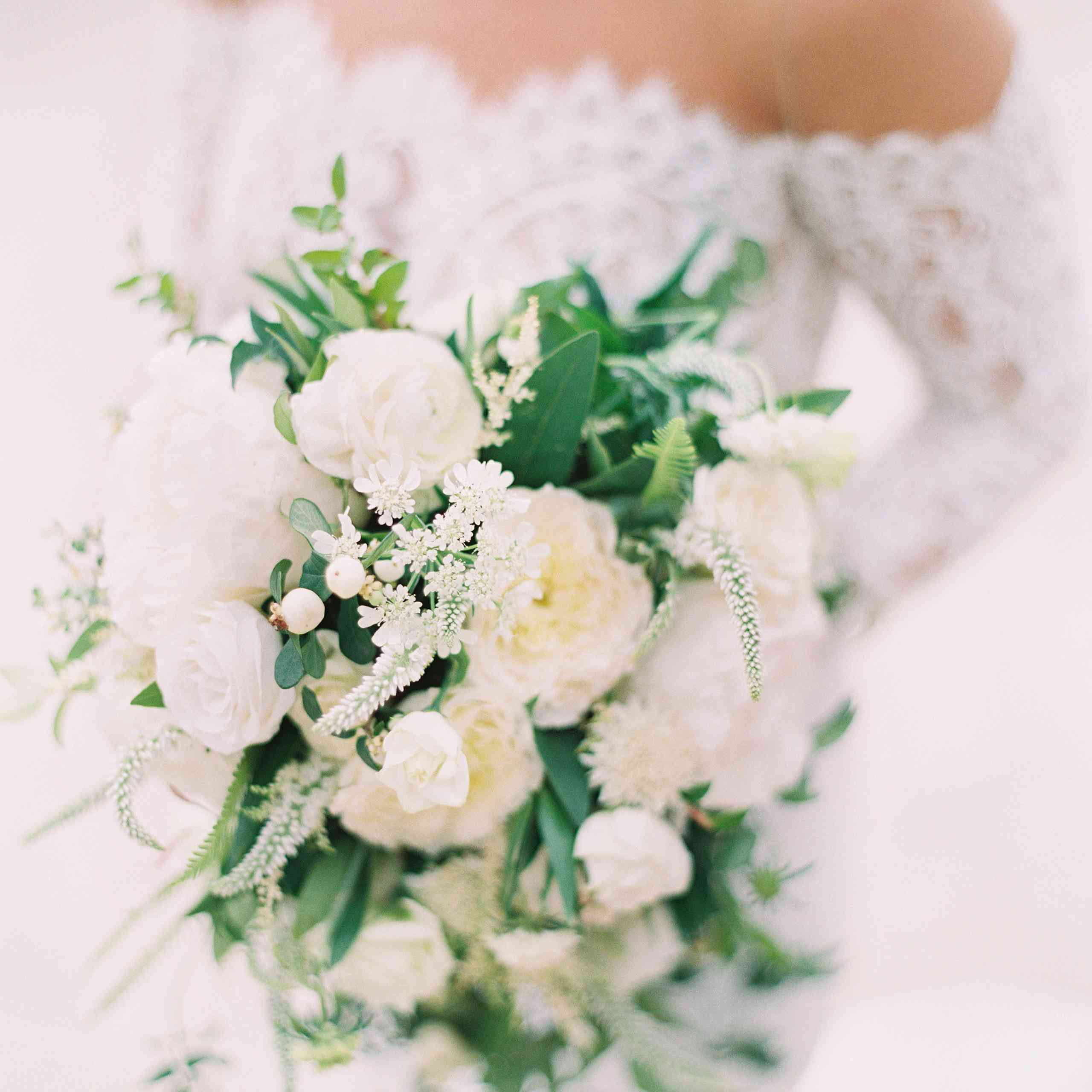<p>A bride holding a green and white bouquet.</p>