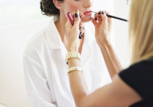 Woman having her lipstick applied by makeup artist