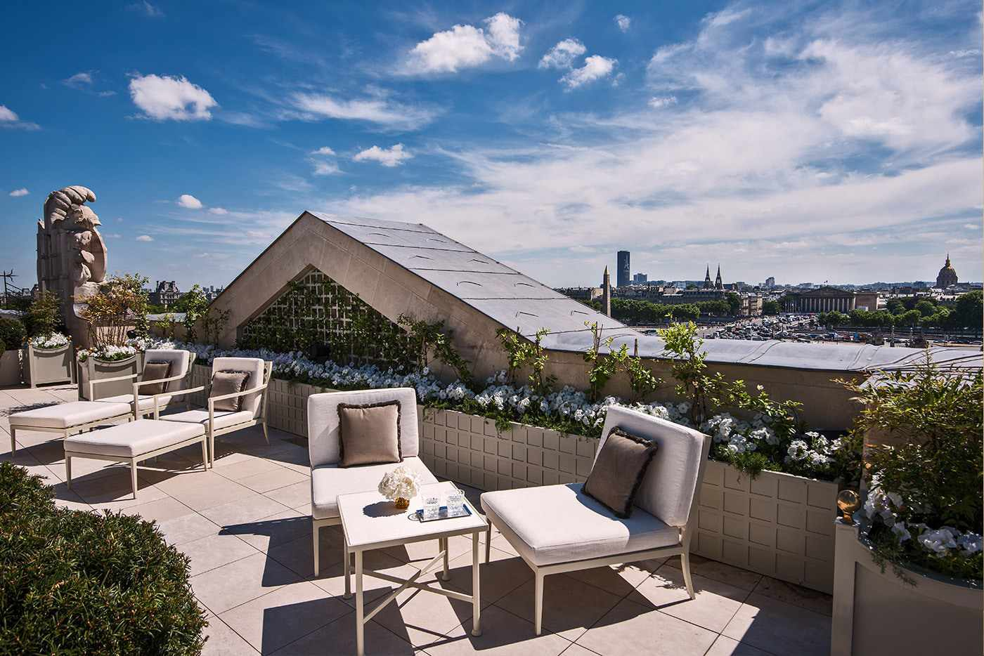 Rooftop of Rosewood Hotel Paris with lounge chairs, shrubbery and white flowers and a view of the city